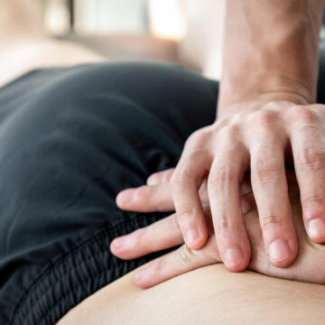Osteopatia2 photo therapist giving lower back sports massage to athlete male patient in clinic 1192496641